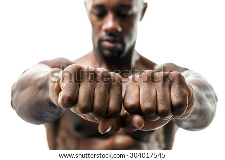 Muscular man of African descent isolated over a white background showing a closeup of his fists and knuckles.  Shallow depth of field. - stock photo