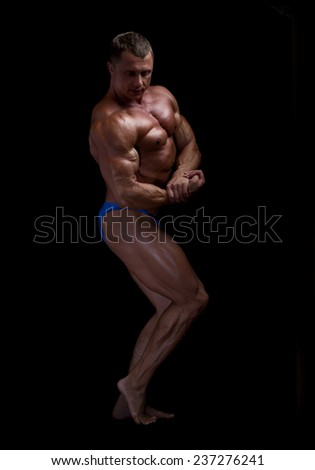 muscular man on a black background - stock photo