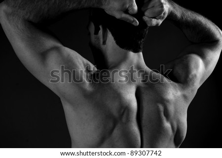 Muscular man on black background - stock photo