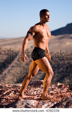 Muscular man on rock. - stock photo