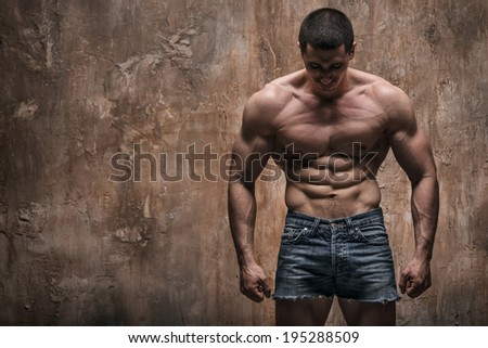 Muscular man on wall background - stock photo