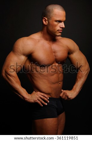 Muscular man poses on gray background