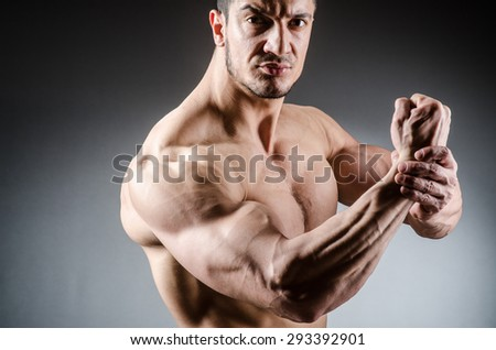 Muscular man posing in dark studio - stock photo