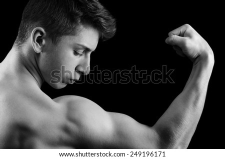 Muscular man posing in studio isolated on black background.