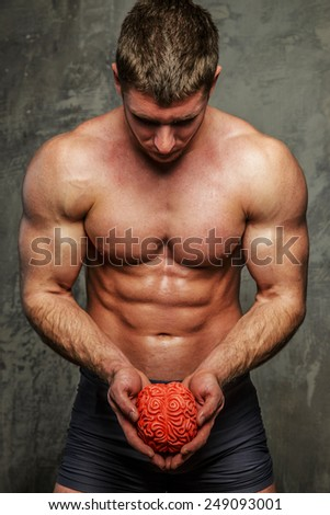 Muscular man posing on gray background with brane in his hands. - stock photo