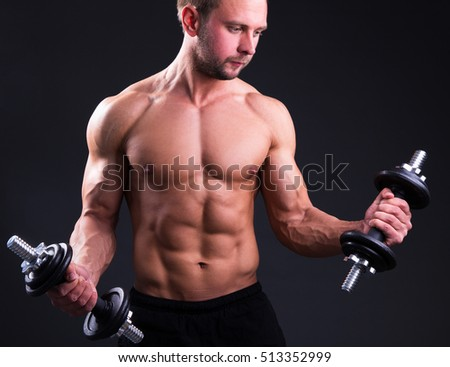 muscular man posing with dumbbells over grey background