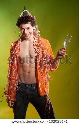 muscular man posing with glass and confetti in studio - stock photo