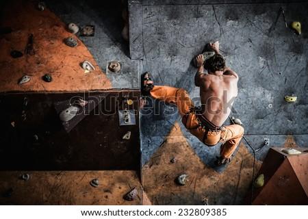 Muscular man practicing rock-climbing on a rock wall indoors  - stock photo