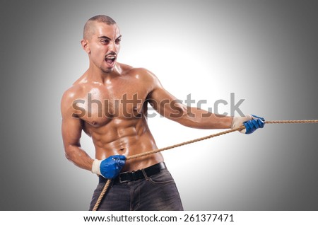 Muscular man pulling the rope - stock photo
