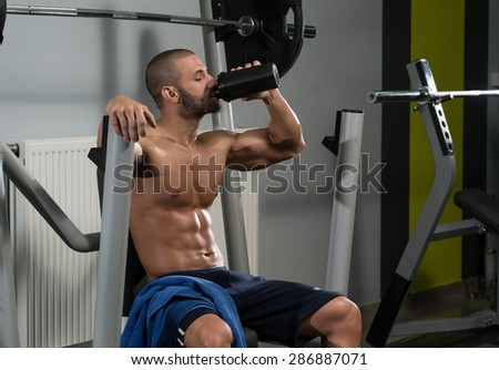 Muscular Man Resting After Exercise And Drinking From Shaker - stock photo