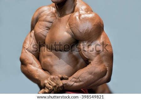 Muscular man's side chest pose. Bodybuilder posing on blue background. Close-up of ripped muscles. Dieting is the key. - stock photo