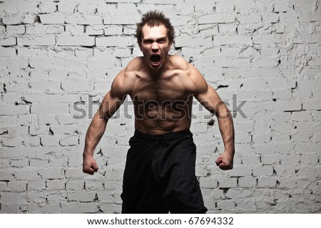 muscular man screaming and roar at brick background - stock photo