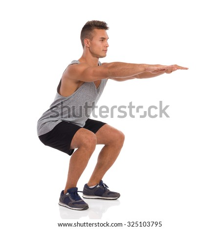 Muscular man showing a squat exercise, side view. Full length studio shot isolated on white. - stock photo