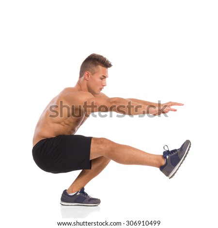 Muscular man showing one leg squat exercise, side view, Full length studio shot isolated on white. - stock photo