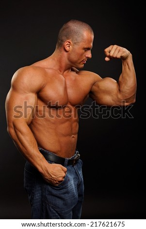Muscular man shows biceps on the dark background