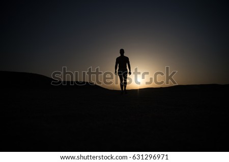 muscular man silhouette on sunset fiery sky background in mountain, sport and recreation, future and success, people and nature, healthy lifestyle, yoga and fitness