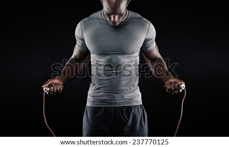 Muscular man skipping rope. Portrait of muscular young man exercising with jumping rope on black background - stock photo