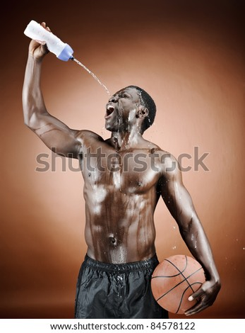Muscular man spraying himself with water after his intense workout - stock photo