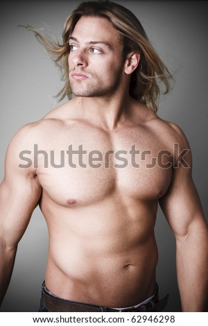 Muscular man standing with a measure tape - stock photo
