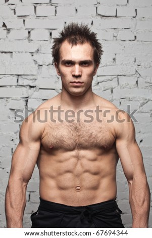 muscular man stands against brick background