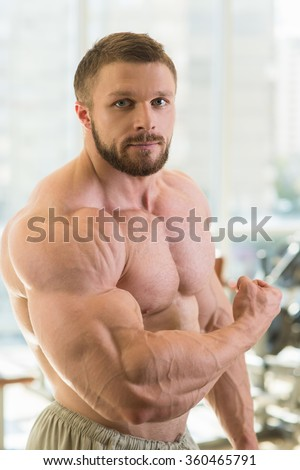 Muscular man. Strong muscular man looking straight at the camera. Bodybuilder with huge muscles. - stock photo