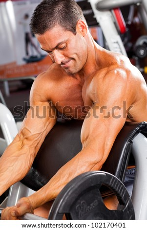 muscular man training with barbell in gym - stock photo