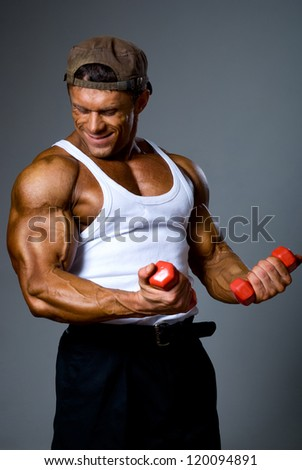 Muscular man training with small dumbbells.comic training - stock photo