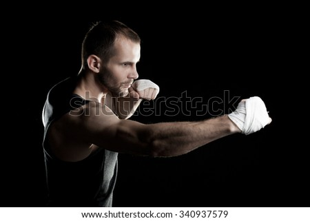 muscular man, tying an elastic bandage on his hand, black background - stock photo