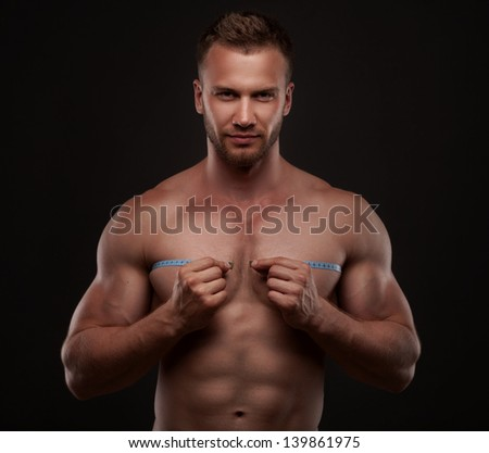 Muscular man use measurement tape, isolated on black background