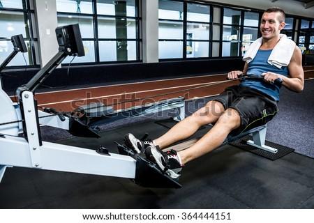 Muscular man using rowing machine at gym - stock photo