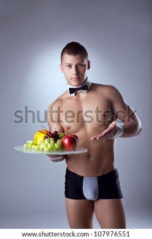 muscular man waiter offer fruits - stock photo