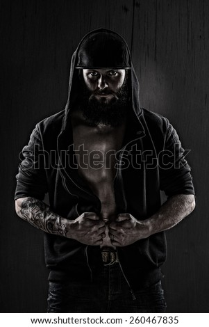 Muscular man wearing a baseball cap and black blouse on grunge wall - stock photo