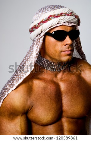 Muscular man wearing a Middle Eastern headdress. - stock photo
