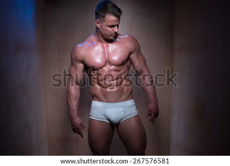Muscular Man Wearing Tight White Boxer Shorts Looking Down and To the Side in Dimly Lit Room - stock photo