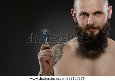 Muscular man with a beard holding a razor - gray background - stock photo