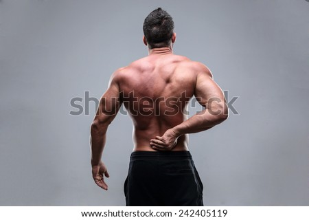 Muscular man with back pain on a gray background - stock photo