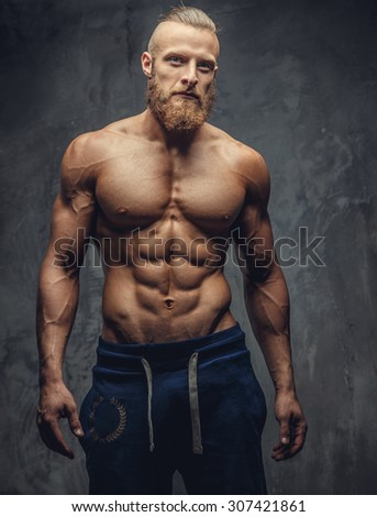 Muscular man with beard showing his great body over grey background. - stock photo