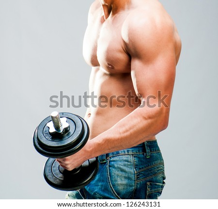 Muscular man with dumbbells on a gray background - stock photo