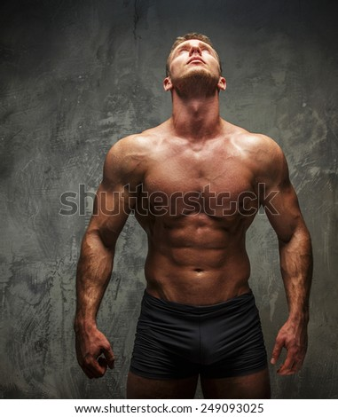 Muscular man with great body relief watching up on white light. Grey background. - stock photo
