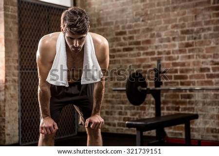 Muscular man with hands on knees at the gym - stock photo