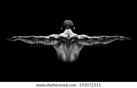 Muscular man with his arms stretched out, rear view of isolated on black background - stock photo