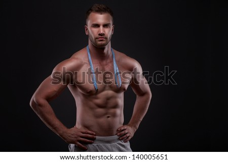 Muscular man with measurement tape, isolated on black background
