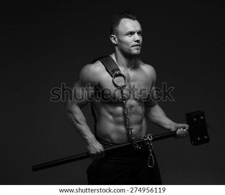 Muscular man with naked torso holding hummer. Black and white shoot - stock photo