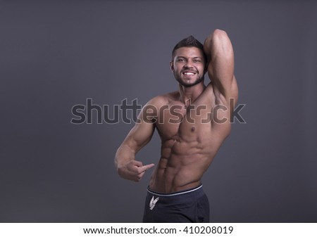muscular man with perfect body is demonstrating its press without a shirt on a dark background