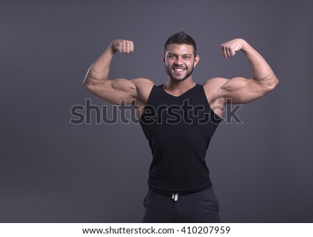 muscular man with perfect body posing in a black shirt on a dark background