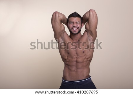 muscular man with perfect body posing without a shirt on a light background - stock photo