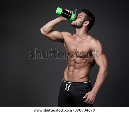 Muscular man with protein drink in shaker over black background - stock photo