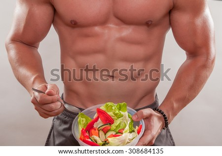 Muscular man with salad.
