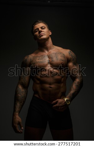 Muscular man with tattooes posing in studio on grey background - stock photo