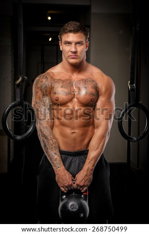 Muscular man with tattos doing exercises in a gym - stock photo